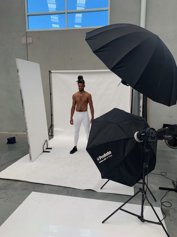 Nickstanding in white compression gear in photography studio