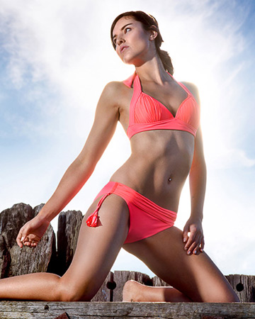 Nicola kneeling in peach swimsuit during fitness photoshoot
