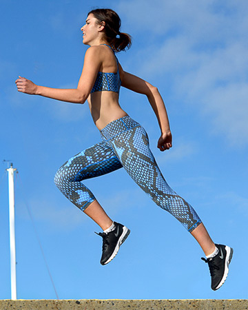 Nicola sprinting in matching blue crop top and blue leggings