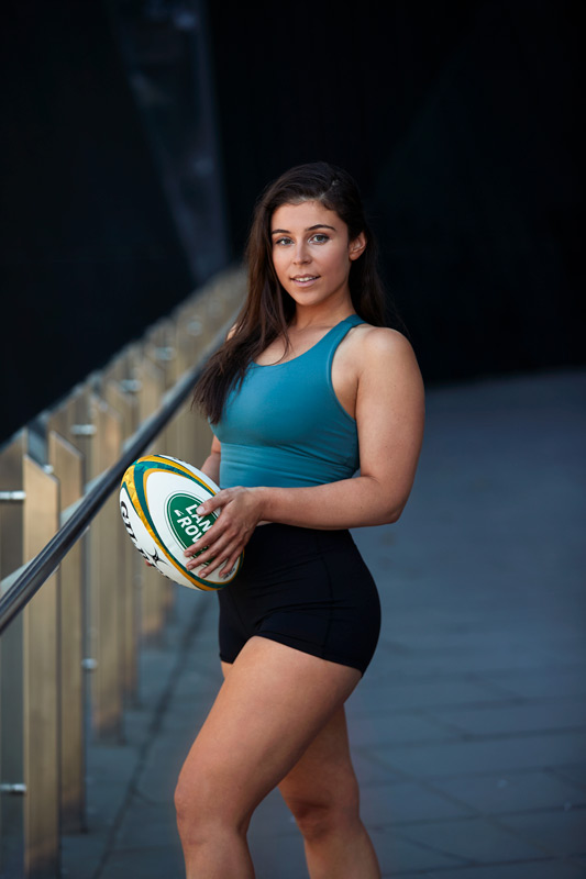 Nicole Melbourne fitness model holding rugby ball