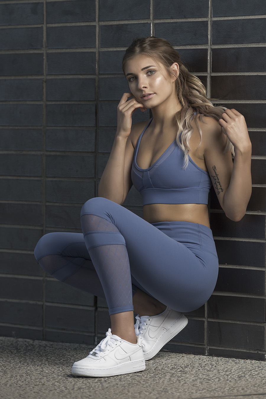 Nikita crouching against a tiled wall wearing a Lorna Jane light blue crop top and matching fabric Leggens