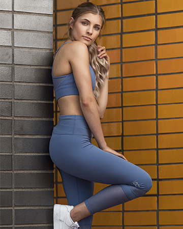 Nikita leaning on a wall wearing a blue crop top and leggins