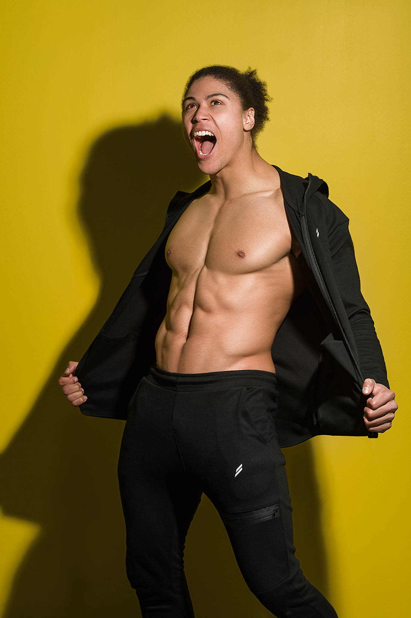 Ossie being animated during his shoot wearing a black zipped Hoody and black pants whilst flexing his abs