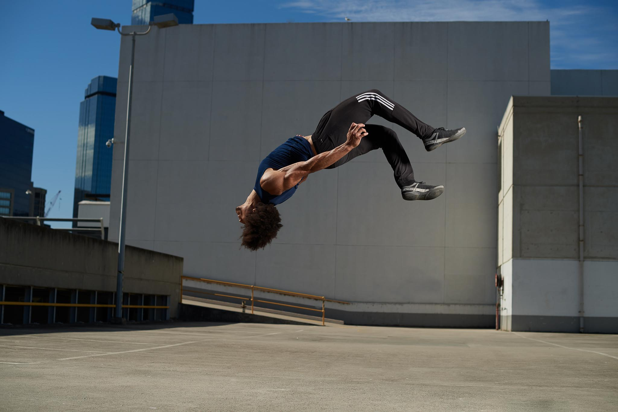 Ossie flying through the air doing a backflip on Melbourne downtown rooftop carpark