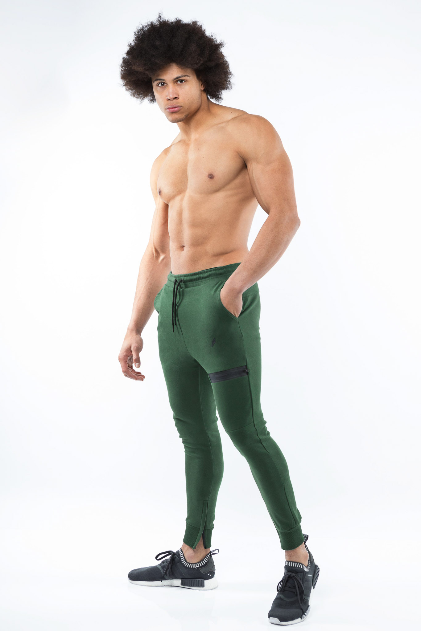 Ossie in a studio with only his green truck suit fitted pants, topless and flexing his abs