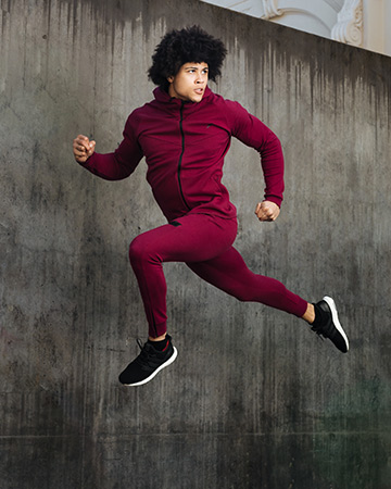 Ossie leaping high in a red doyoueven tracksuit