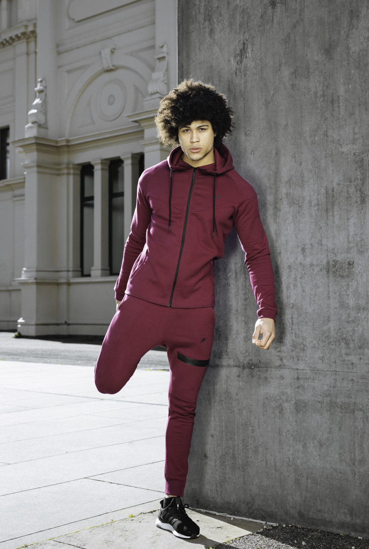 Ossie stretching his quad wearing a maroon doyoueven full tracksuit
