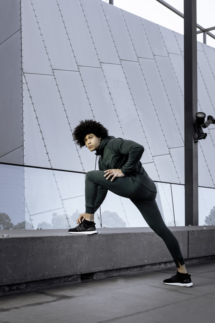 Ossie stretching, lunging onto a concrete platform wearing a green for tracksuit
