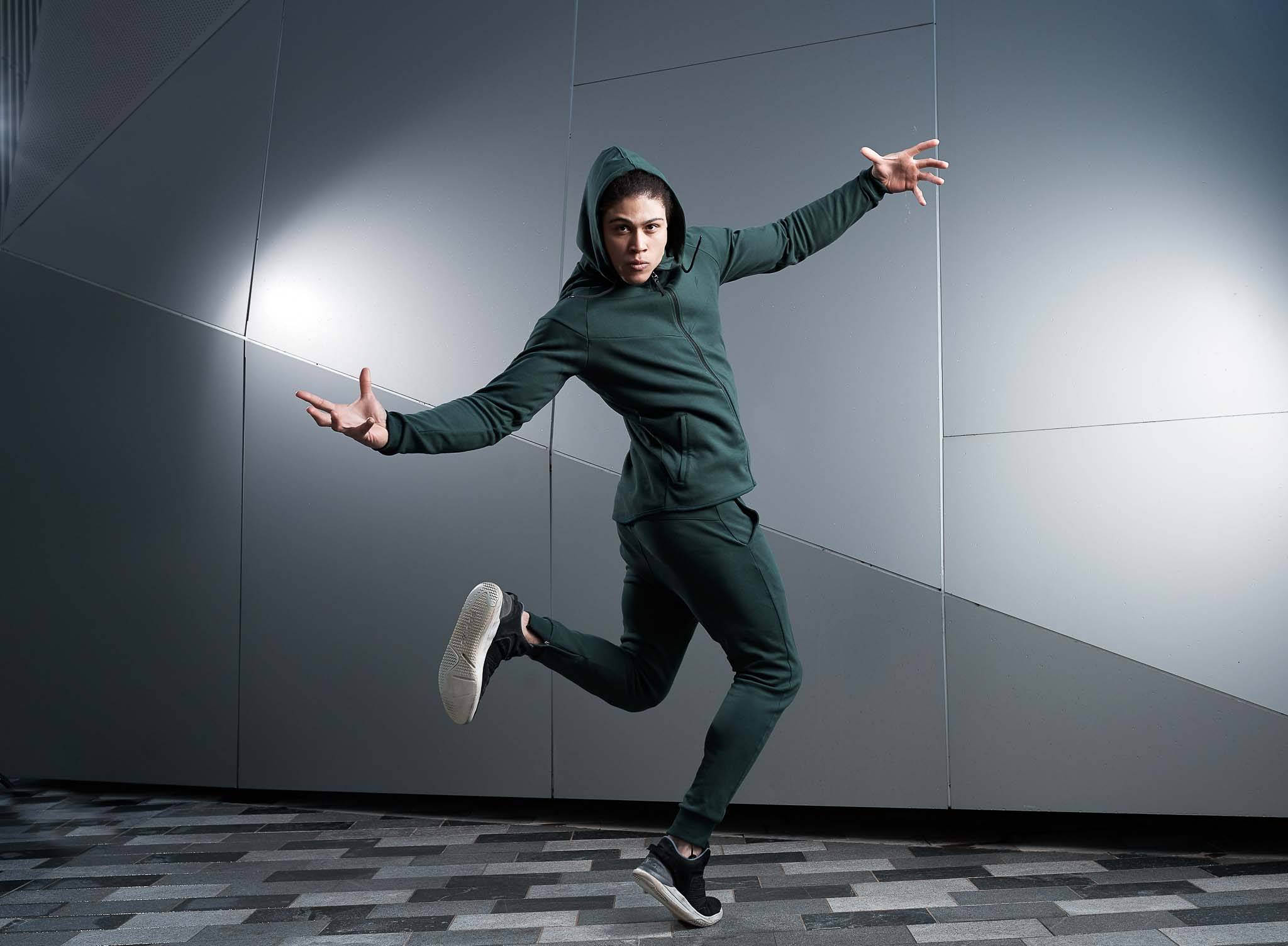Ossie with his tracksuit hood over his head dancing in green full trucksuit