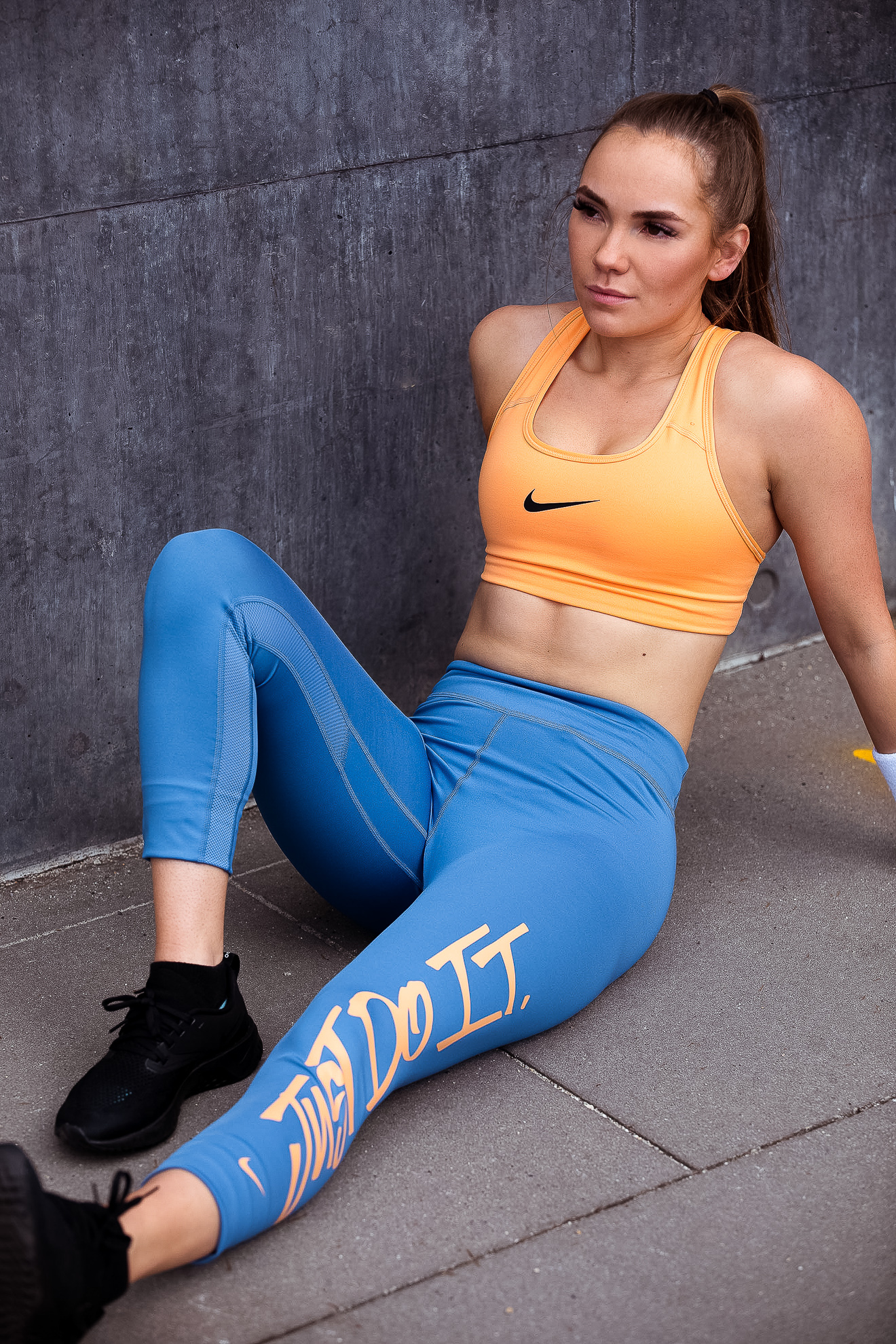 Ruby seated wearing Nike just do it blue tracksuit pants and orange Nike crop top