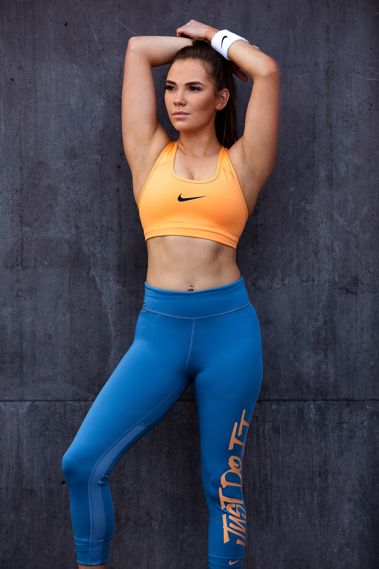 Ruby standing wearing Nike just do it blue leggings and Nike orange top standing in front of a grey concrete wall
