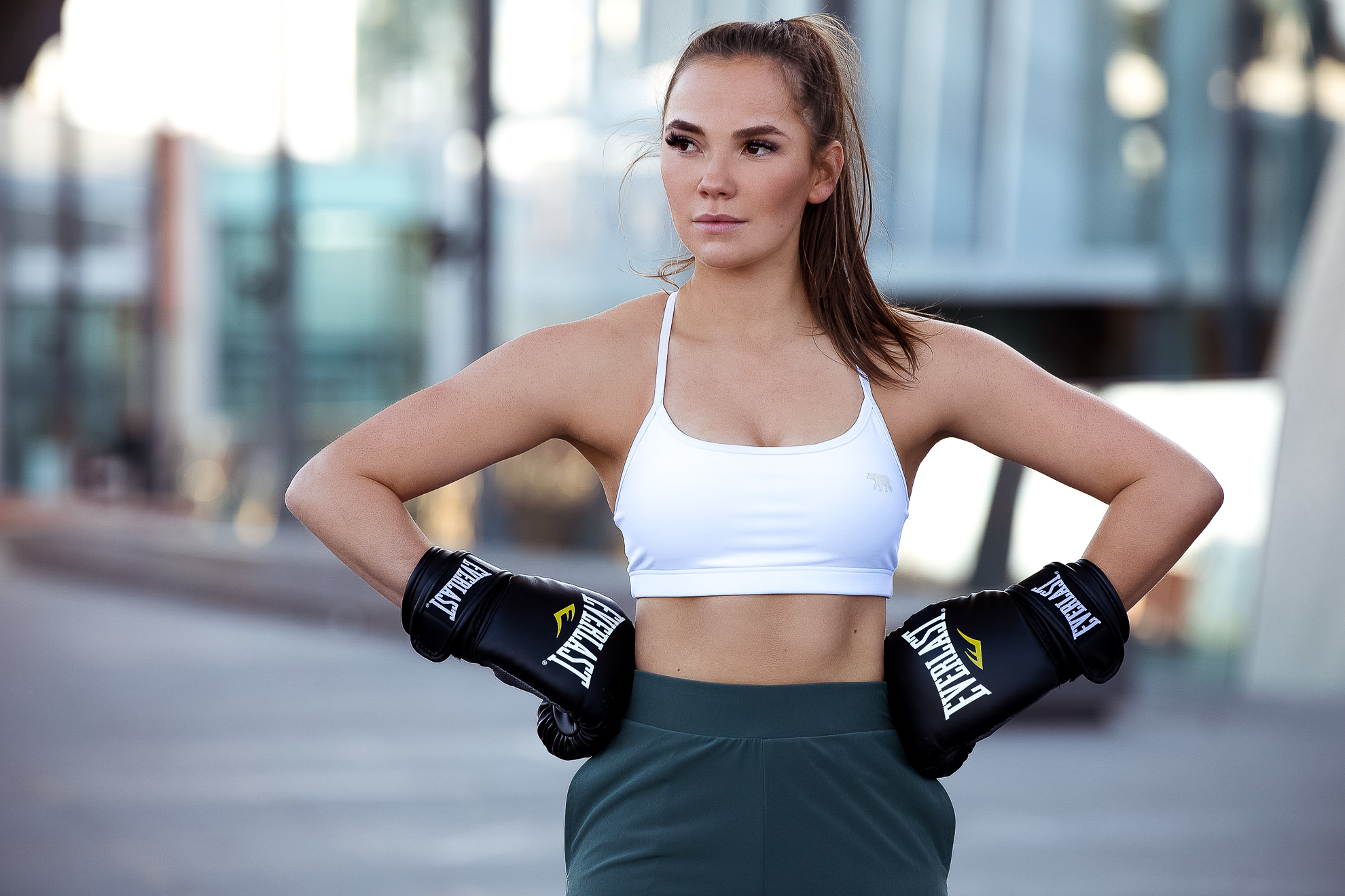 Ruby standing with her hands on her hips wearing Everlast boxing gloves with white crop top