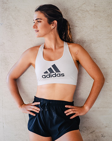 Sam R posing with her hands on her hips wearing a grey adidas crop top