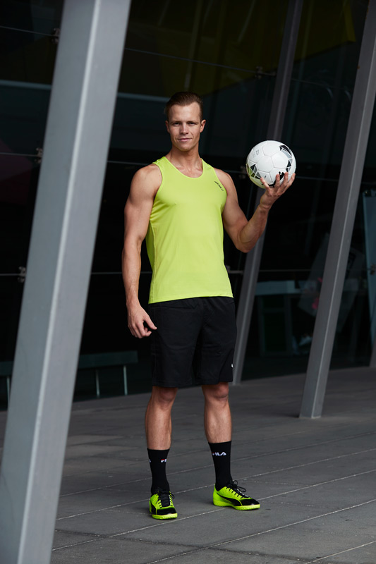 Sam holding a soccer ball during his fitness shoot in Melbourne at the exhibition building