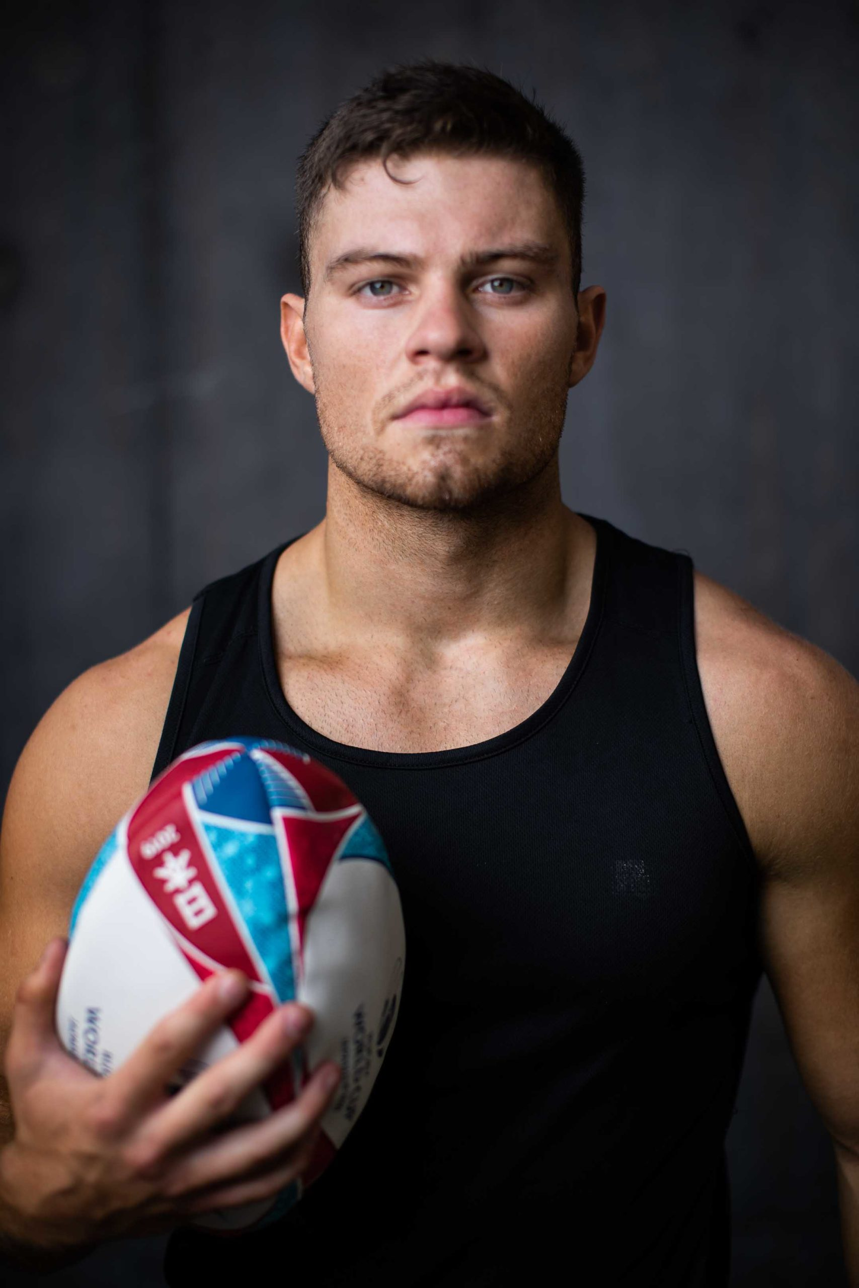 Sean holding a rugby ball whilst wearing a black singlet