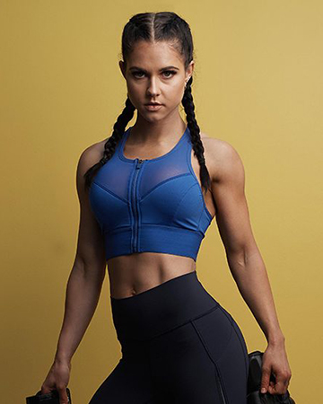 Sharelle wearing black fitted athletic workout pants and crop top purple fitness top