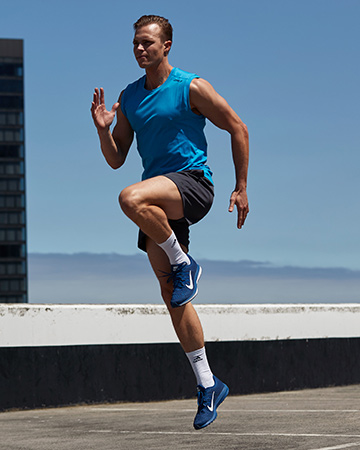 Some sprinting through a carpark wearing a blue T-shirt and black shorts
