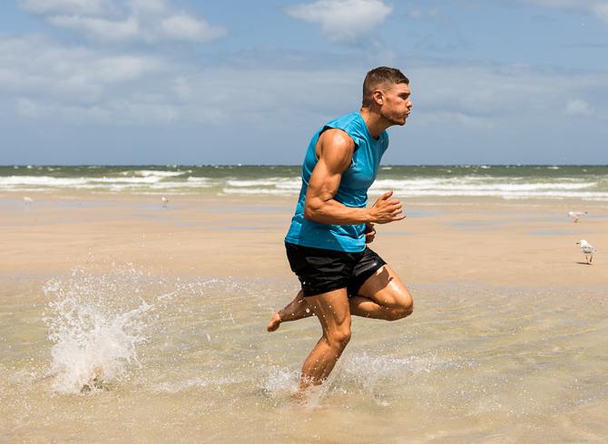 Thomas running through water in Adelaide beach