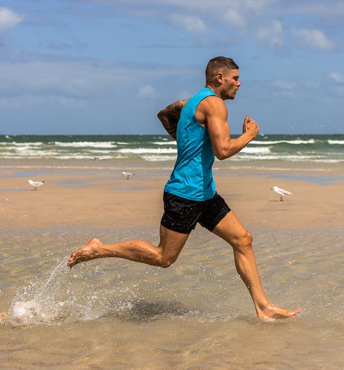 Thomas running through water in Glenelg beach Adelaide