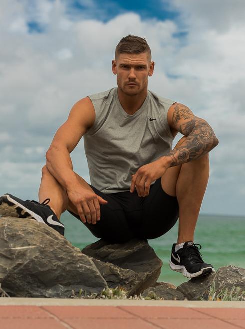 Thomas wearing Nike garments seated on walk way