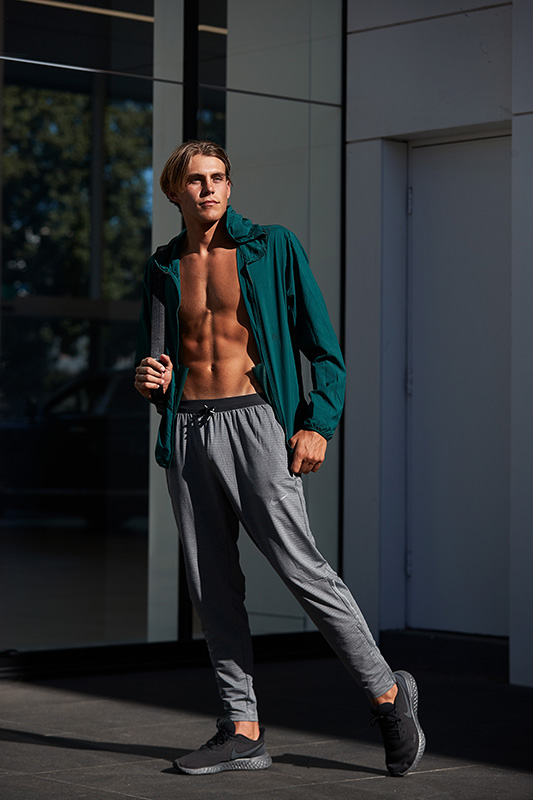 Ty Sydney fitness model posing with green Lululemon tracksuit top and grey Lululemon trousers