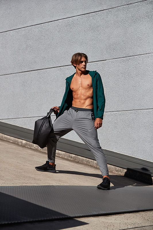 Ty Sydney male fitness model standing on car park ramp wearing open Lululemon green zip top with grey Lululemon loose fitting pants