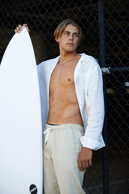 Ty holding surfboard wearing white shirt open with linen pants
