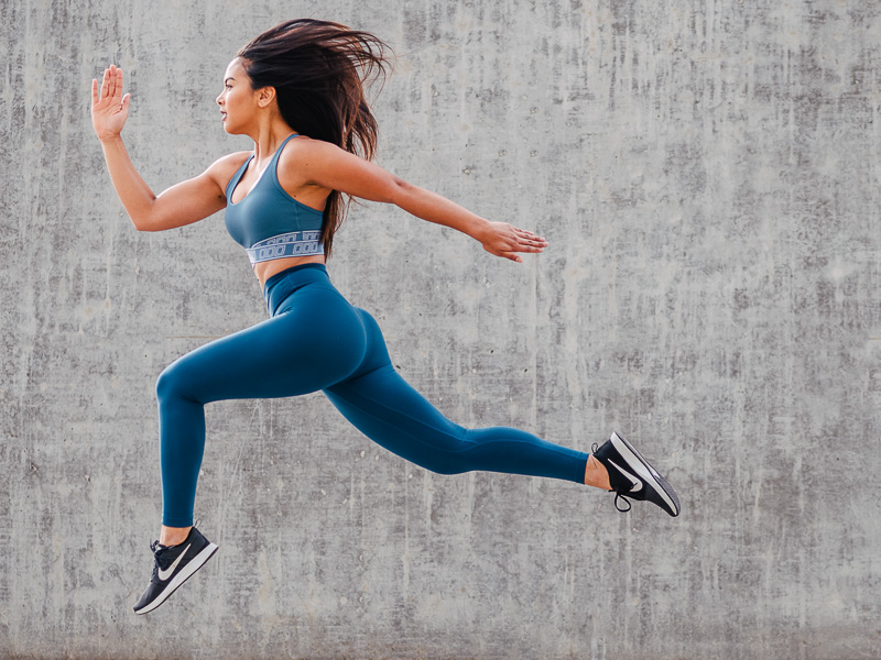 Woman Jumping in sportswear in front of stone background