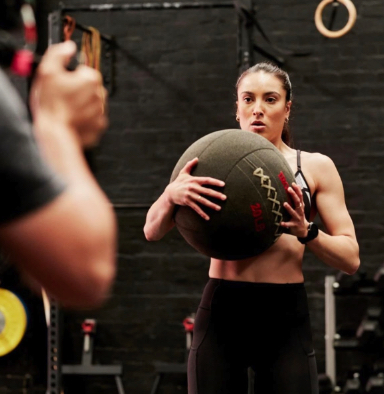 woman in gym holding medicine ball
