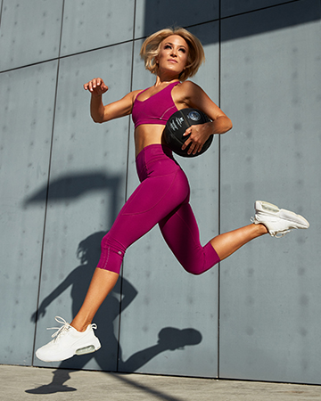 Alexandra jumping with a medicine ball under her arm