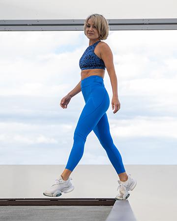 Alexandra wearing her blue fitness garments walking on Southport boardwalk