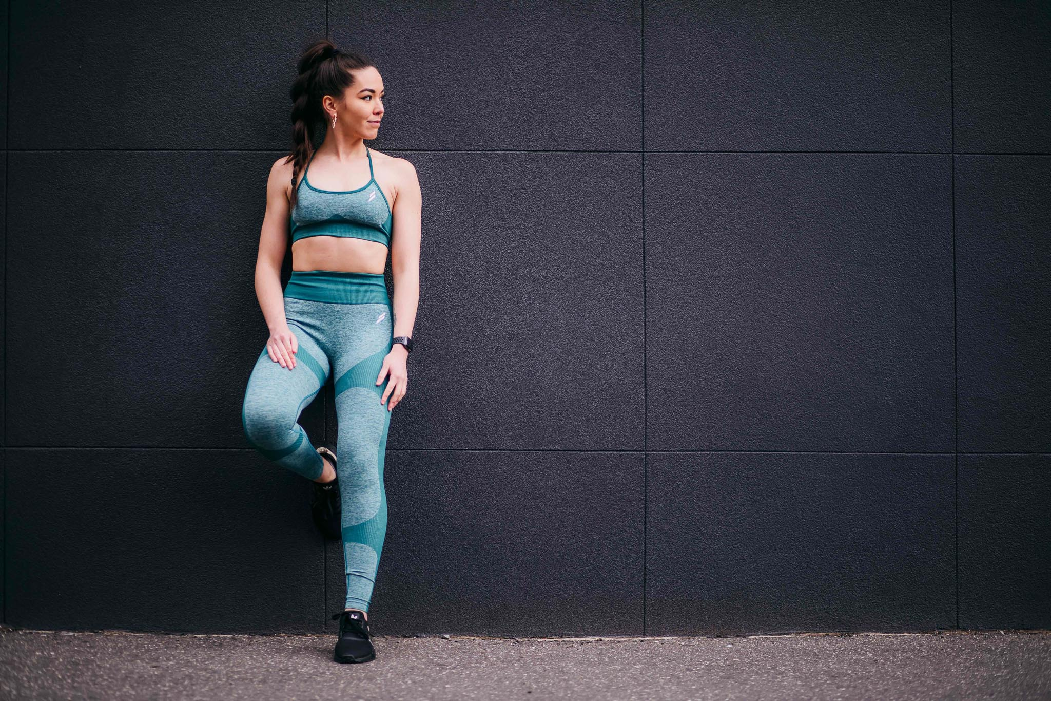 Deborah wearing fitness clothing leaning against a concrete wall