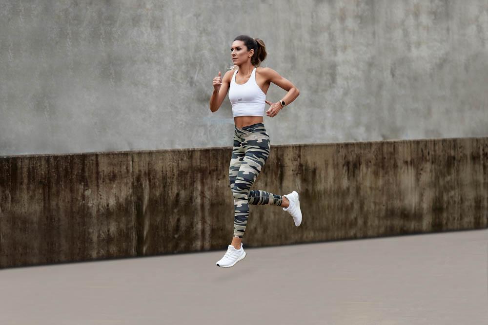 Roula running in her camouflage pants enjoying her fitness portfolio shoot