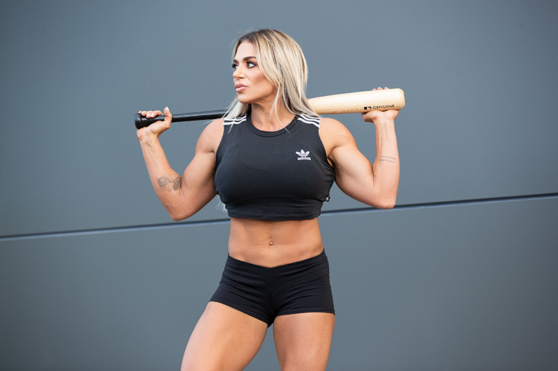 Suzan posing holding a baseball bat during her fitness year