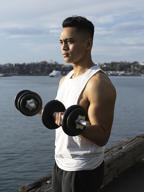 Christian NSW fitness male model curling dumbbells