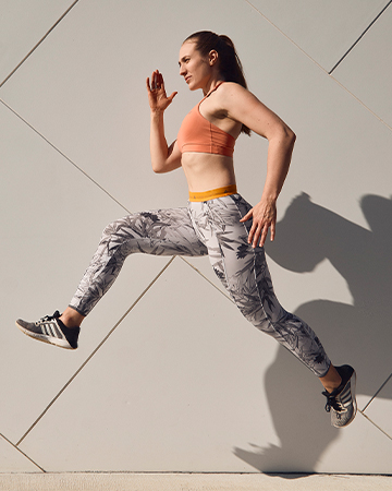 Georgina Sydneys Elite female fitness model running beside a concrete wall