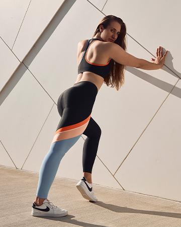Georgina Sydneys Elite female fitness model stretching against a concrete wall 1