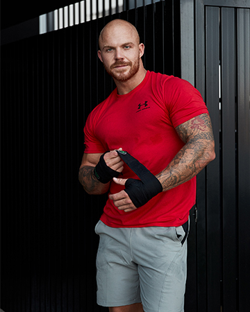 Dylan professional fitness model standing wrapping his hands with boxing wraps