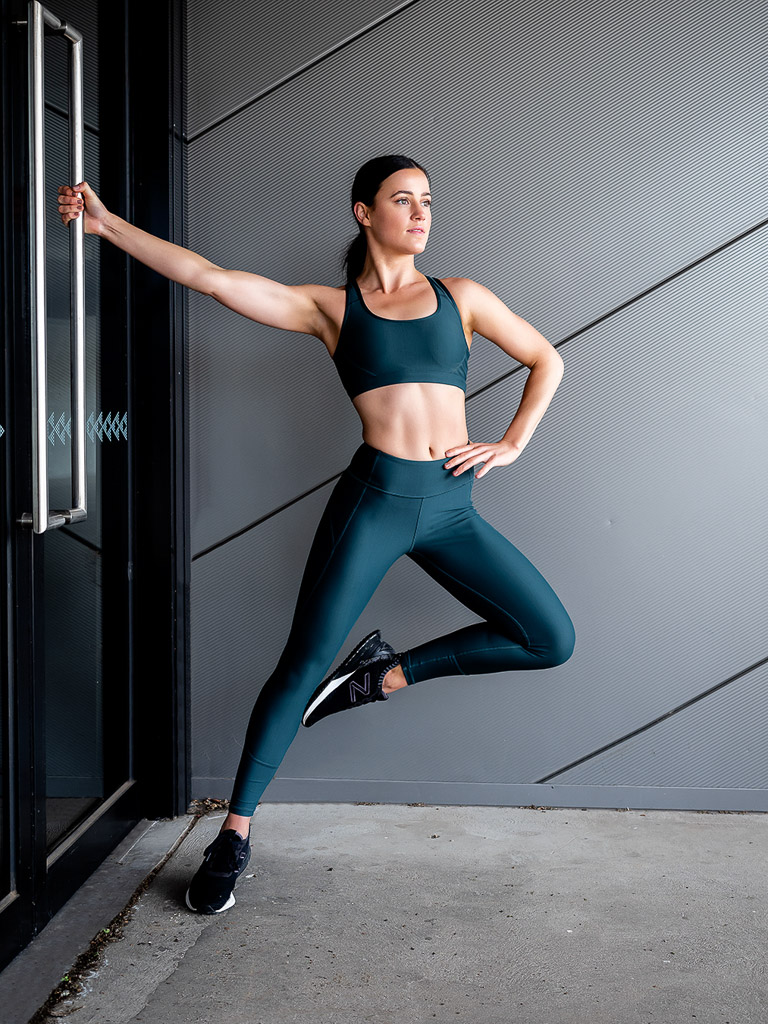 Amy Melbourne Fitness Model and High Level Dancer hanging from a door handle 1