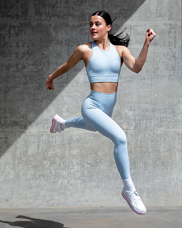 Amy jumping in light blue fitness garments