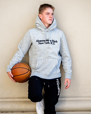 Austin Melbourne teen fitness model posing holding a basket ball leaning.against a concrete wall