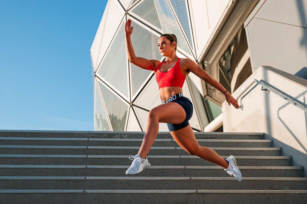 Christine Melbourne young female fitness model jumping laterally on a set of steps