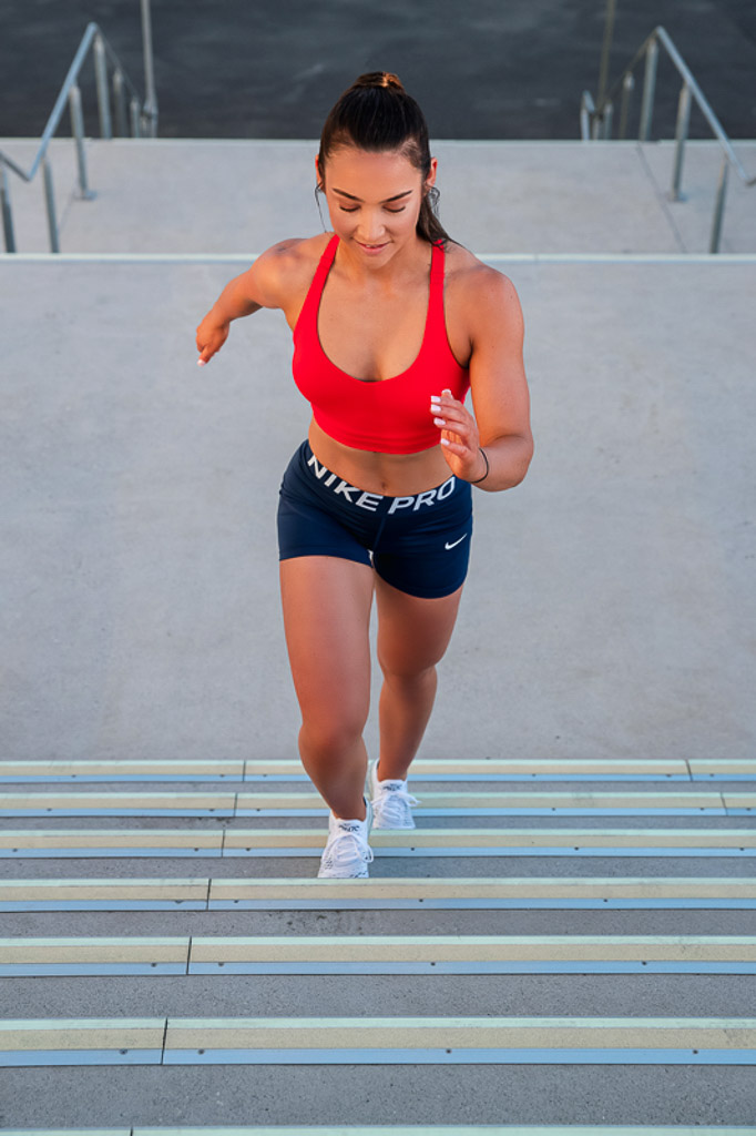 Christine Melbourne young female fitness model running up a set of steps