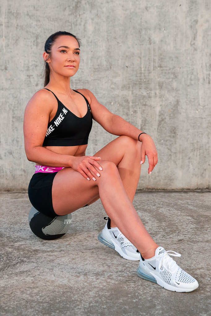 Christine Melbourne young female fitness model seated on a medicine ball