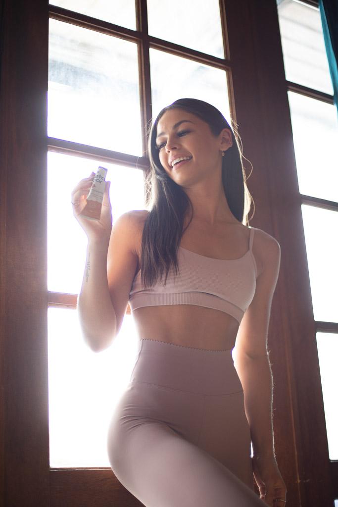 Elly Australian elite fitness model tasting testing the new FEVA Bar near a bay window