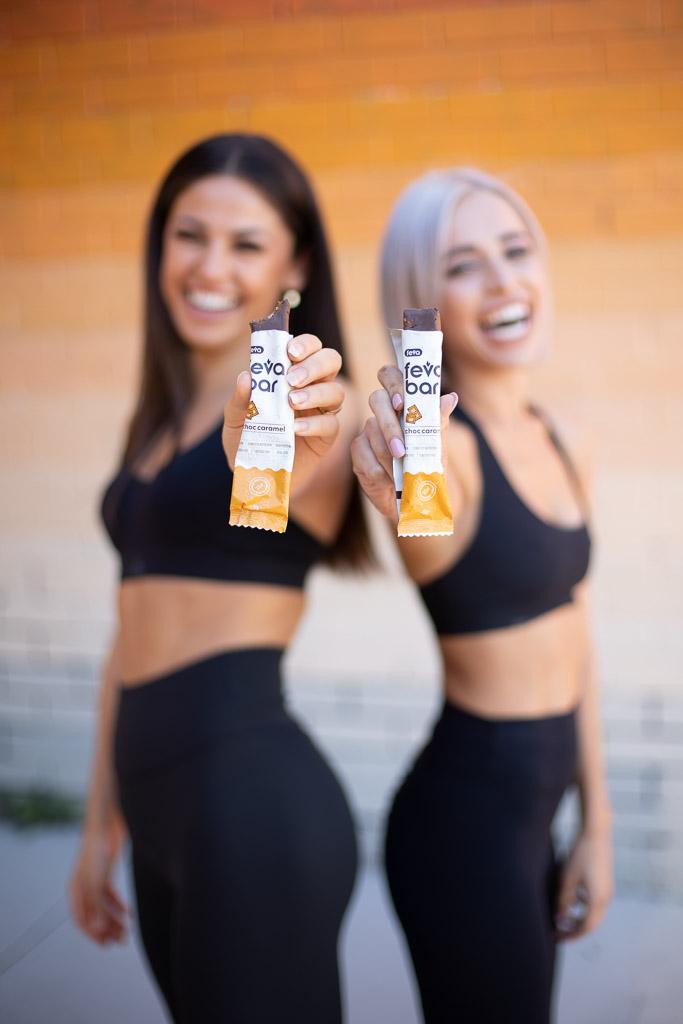 Elly Australian elite fitness model tasting testing the new FEVA Bar with a fellow model