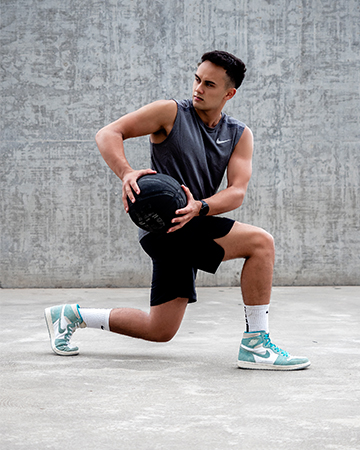 Professional formula one driver Luis lunging holding a medice ball