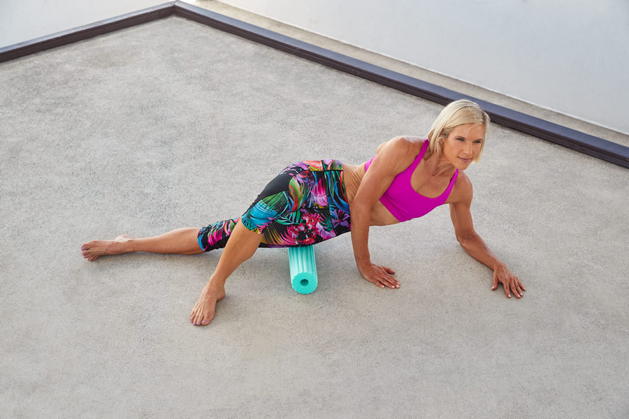 Queenslands mature female fitness model stretching on a foam roller