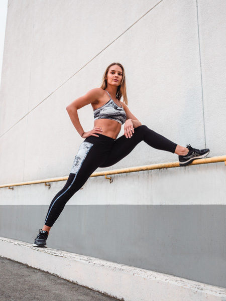 Ruby Melbourne female fitness model strecthing against a concrete wall 1