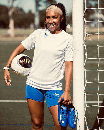 Samantha Melbournes professional soccer player holding her soccer boots
